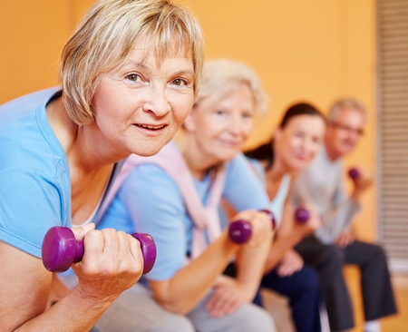 Senior vrouw met halters doen terug opleiding in een fitnesscentrum