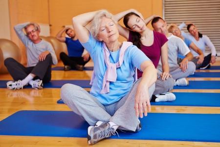 estiramientos: Grupo haciendo ejercicios de estiramiento en la clase de entrenamiento de nuevo en un gimnasio