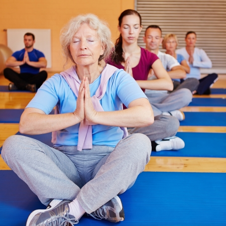 meditation woman: Senior woman doing relaxation exercise in yoga class in a gym Stock Photo
