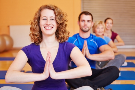 yoga man: Happy woman smiling in yoga class in a fitness center