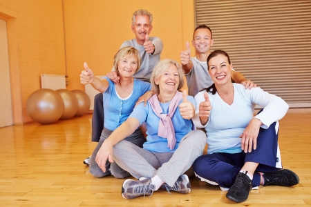 Happy group of seniors in a fitness center holding their thumbs up photo