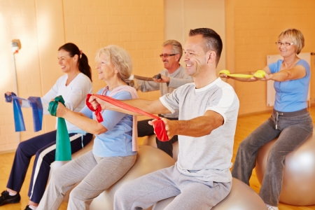 healthy seniors: Reha sports for group of happy seniors in fitness center Stock Photo