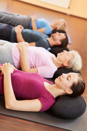 Mixed group in yoga class relaxing in a fitness center photo