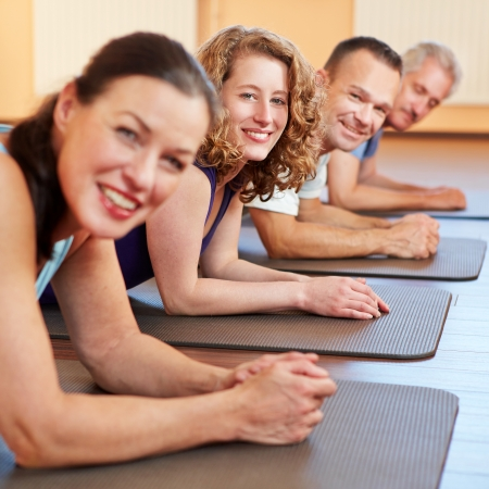 Happy men and woman laying smiling on gym mats in a fitness center photo