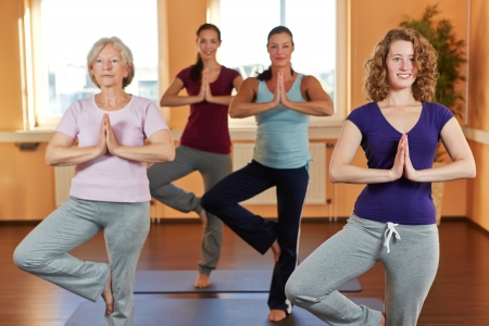 yoga class: Four women in yoga course meditating in a fitness center Stock Photo