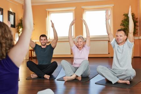 terapia de grupo: Grupo ejercicio con las piernas cruzadas con preparador f�sico en un gimnasio