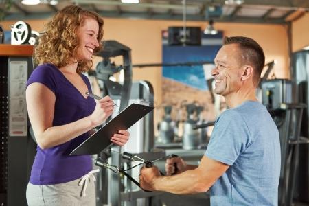 aide � la personne: L'homme exerce sur la machine de c�ble dans le gymnase et l'�coute de pr�parateur physique des femmes
