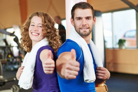 Happy smiling young couple in health club holding their thumbs up