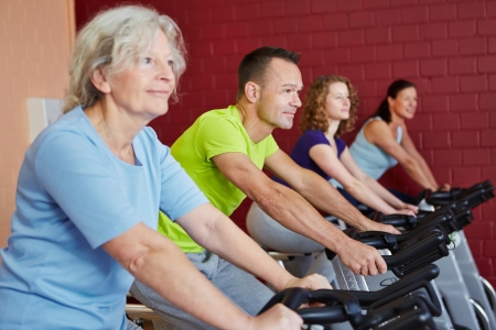 overweight man: Group riding spinning bikes in a fitness class in health club Stock Photo