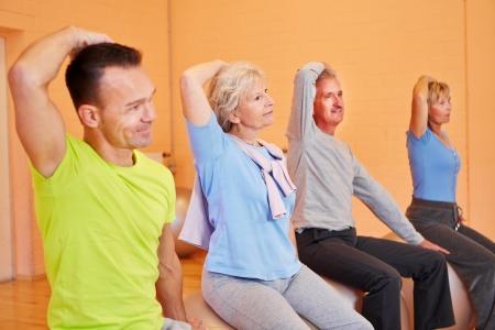 senior yoga: Group of senior people exercising in gym on fitness balls Stock Photo