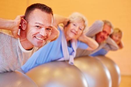 gimnasia: Grupo feliz con las personas mayores en un curso de vuelta en gimnasio