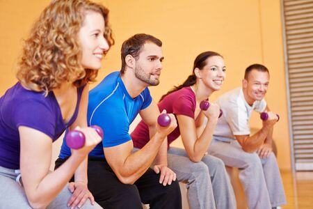Young smiling sports group exercising with dumbbells in a gym Stock Photo - 16490252