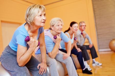 senior citizens: Group of senior people doing back training exercises in a gym