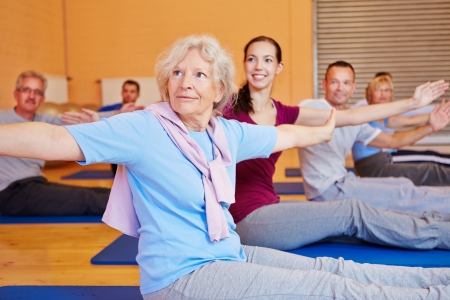 Senior woman doing gymnastics exercises in back training course in gym photo