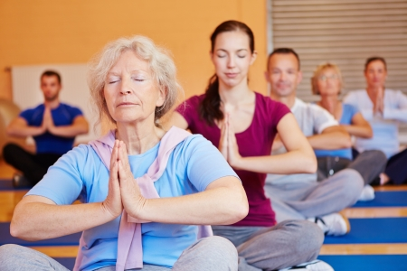 man meditating: Senior woman relaxing in a yoga class in gym