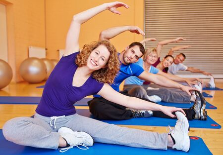 Smiling group doing stretching exercises in back training class in a gym photo