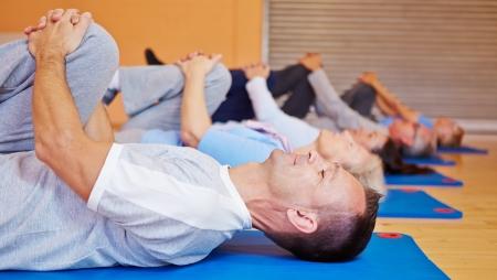 back exercise: Group doing back training exercises in fitness center