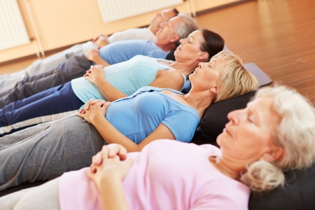 man meditating: Elderly group doing neditation and relexation in a fitness center Stock Photo