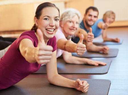 Happy group holding their thumbs up in a fitness center Stock Photo