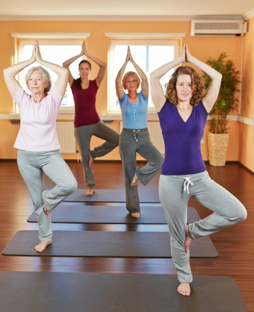 Women in yoga class doing the tree (Vrikshasana) in a fitness center photo