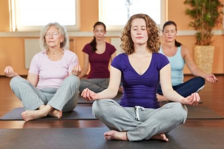 terapia de grupo: Grupo de mujeres que hacen ejercicios de relajación de yoga en el gimnasio