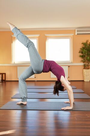 Young flexible woman doing the yoga wheel exercise Chakrasana photo
