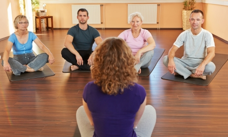therapy group: Fitness coach giving group yoga instructions in a gym Stock Photo