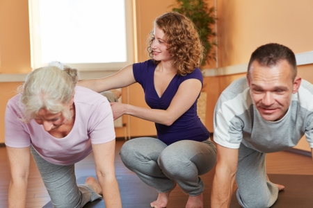 Fitness trainer with senior sports group giving instructions to elderly woman photo