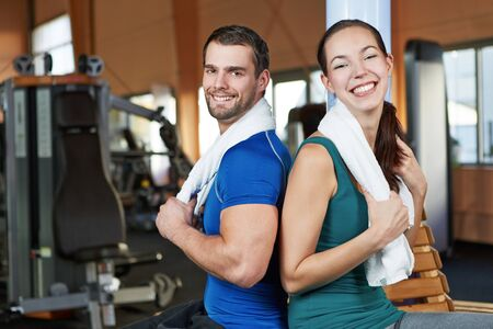 health club: Young happy couple sitting back to back in a health club