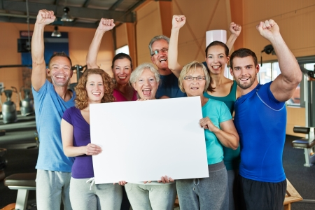 sport celebration: Cheering group doing advertising for fitness center with empty white sign