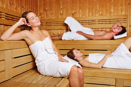 Three young people sitting relaxed in a sauna photo