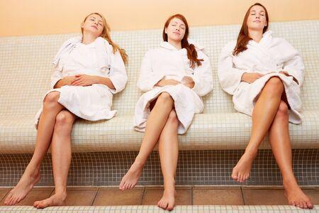 bathrobes: Tres mujeres j�venes atractivas en un banco de calor relajante Foto de archivo