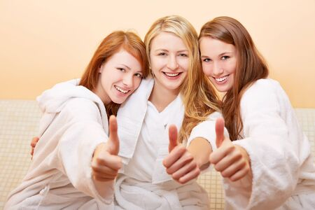 Three happy women in a bath holding her thumbs up photo