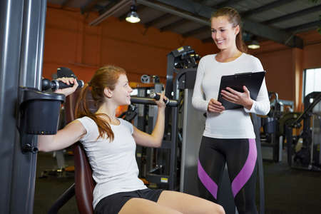 fitness center: Woman in fitness center on a shoulder press listening to female trainer Stock Photo