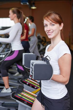 crosstrainer: Happy woman near a crosstrainer lifting weights in a fitness center Stock Photo