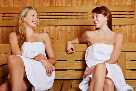 Two women sitting smiling in sauna and talking to each other photo