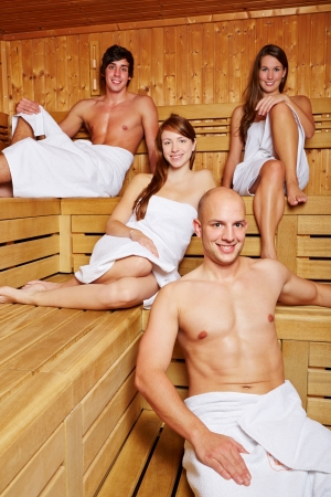 Happy men and women sitting in a mixed sauna photo