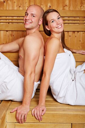 Happy smiling couple sitting in the sauna of a hotel photo