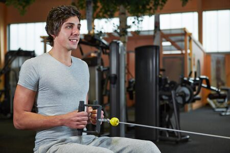 Young man exercising on cable machine in a sport studio Stock Photo - 16523695