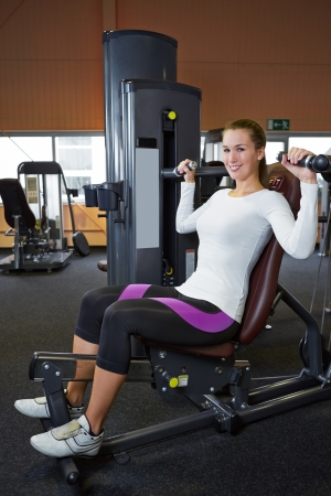 Smiling woman doing back exercises in fitness center on a shoulder press Stock Photo - 16523694