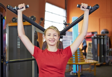 Smiling woman doing back exercises in fitness club on a shoulder press Stock Photo - 16523691