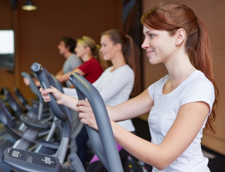 crosstrainer: Young woman exercising on a crosstrainer in fitness center Stock Photo