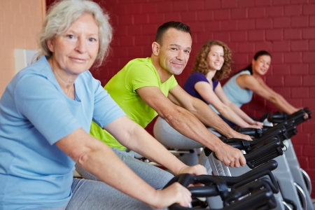 Group doing fitness training with spinning bikes in a health club