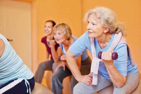 Smiling senior woman in a group doing back training exercises with dumbbells Stock Photo