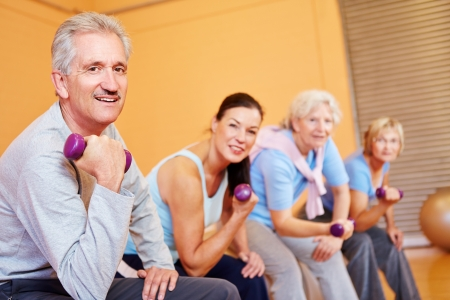 Elderly group doing senior sports with dumbbells in fitness center photo