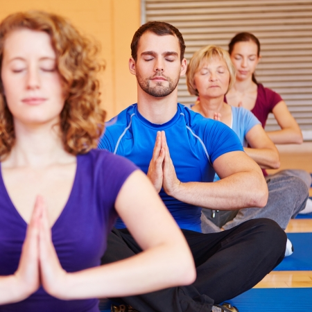 Meditation in a mixed yoga group in a fitness center photo