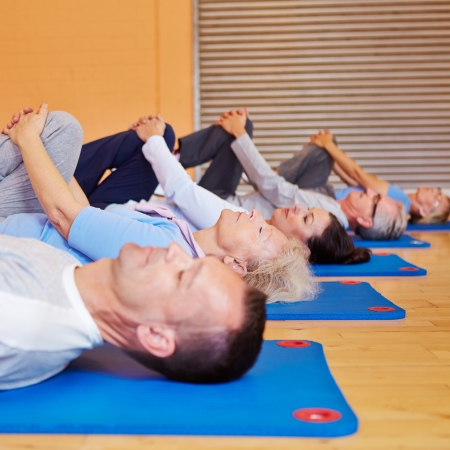Senior people doing stretching exercises in a sports class in gym photo