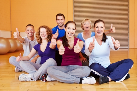 Cheering sports group holding thumbs up in a fitness center photo