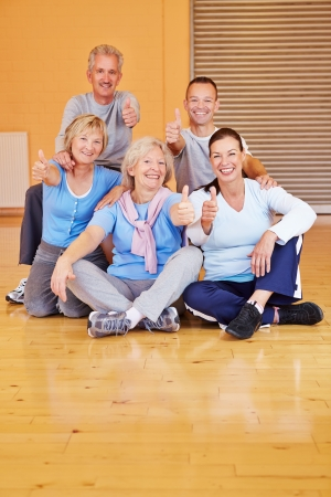 senior fitness: Many happy seniors holding their thumbs up in a sports club