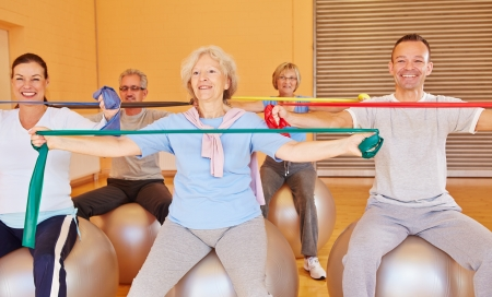 rehab: Group of happy senior people doing back training with exercise band in gym